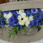 Hat box brimming with cornflowers and roses.